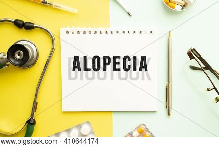 Text Alopecia On Notebook With Stethoscope And Pen On Yellow Background. Medical Concept.