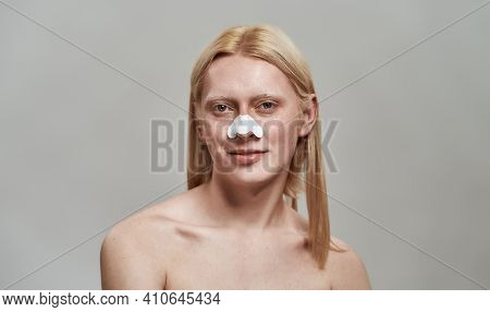 Groomed Young Caucasian Boy With Long Fair Hair Using Nose Pore Cleansing Strips And Smiling At Came