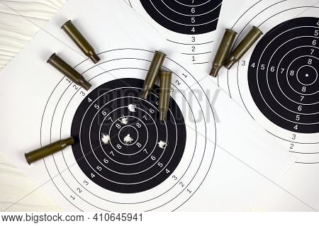 Many Bullets On Shooting Targets On White Table In Shooting Range Polygon. Training For Aiming And S