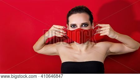 Woman Holding Protective Red Face Mask And Looking Forward On Red Background