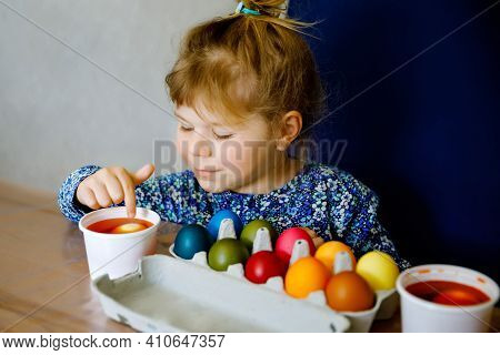 Excited Little Toddler Girl Coloring Eggs For Easter. Child Looking Surprised At Colored Egg Hoardin