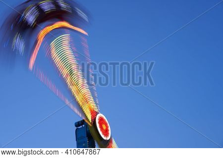 Amusement Park Blurred Effect. Abstract Illuminated Background Spinning Defocused Carnival Carousel