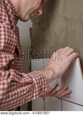 Tiler in red tartan shirt  installing white ceramic tiles on a wall