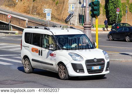 Rome, Italy - August 1, 2014: White Taxi Car Fiat Doblo In The City Street.