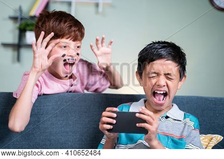 Young Kid With Face Painting Fools Or Making Prank To His Brother While He Is Busy On Mobile By Sudd