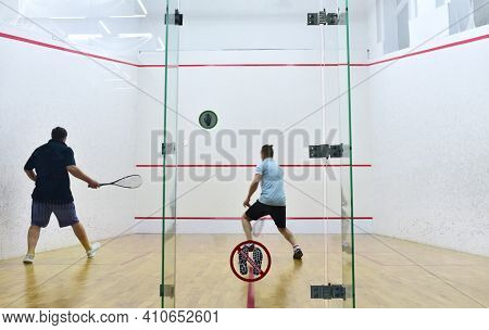 Squash Player In Action Reaching On Squash Court. Squash Players On Tournament. Sports Equipment And