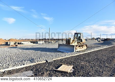 Bulldozer Moves Gravel During On Road Work At Construction Site. Dozer Leveling Stones For Laying As