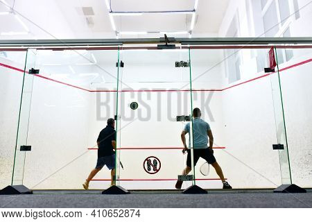 Squash Player In Action Reaching On Squash Court. Out Of Focus