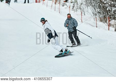 Downhill Skier. Snowboarders And Skier Ride On Snow In The Mountains. Downhill Ride. Adventure Skier