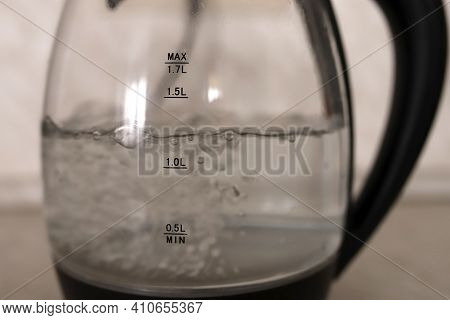 Transparent Kettle In The Kitchen. Water Boils In A Transparent Teapot With A Black Handle. Boiling