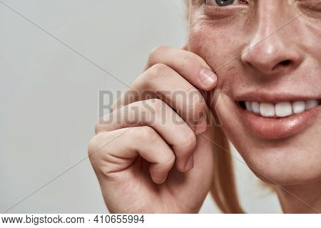 Close Up View Of Young Caucasian Man With Long Fair Hair Tightening His Cheek And Smiling To Side Wh