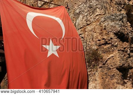 Turkish Flag On The Rocky Mountain Background. Close Up Of Flag Of Turkey And Rocky Cliff. Tourism C