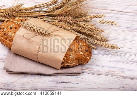 One Loaf Of Freshly Baked Buckwheat Bread In A Paper Bag Isolated. Loaf Of Fresh Bread On White Back
