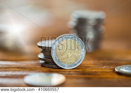 Two Euro Coin Standing Erected Near To Stack Of Money Arranged In Column