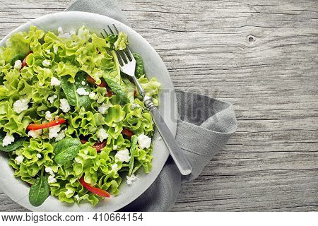 Healthy Green Salad With Fresh Cheese On Wooden Table Background Close Up. Healthy Salad Meal.