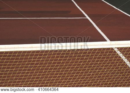 Tennis Net On Empty Court With Brown Surface Front View Close Up