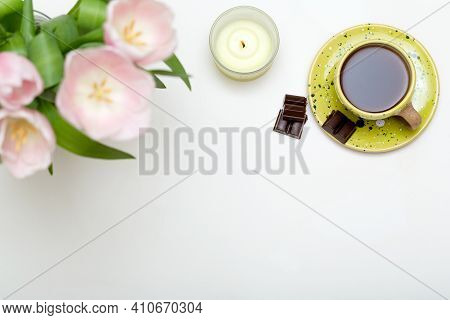 Spring Cozy Composition. Pink Tulips, Chocolate, Coffee Cup, Candle On White Background. Spring Conc