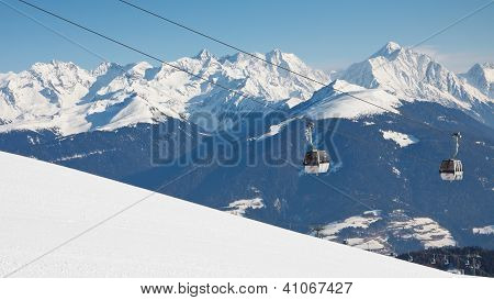 Gondola ski lift and snow covered mountain range in the background. poster