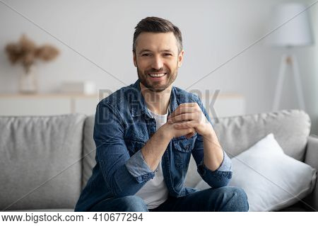 Handsome Middle-aged Bearded Man In Casual Posing In Living Room At Home, Smiling At Camera. Happy C