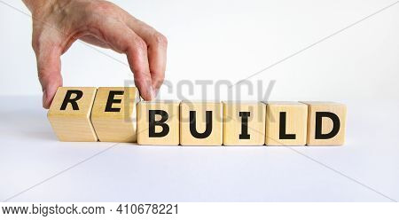 Time To Rebuild Symbol. Businessman Turns Wooden Cubes And Changes The Word 'build' To 'rebuild'. Be