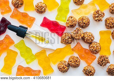 Gummy Bears, Cbd Cookies And Thd Oil Dropper In White Backdrop. Thd Or Cannabis Sweets In Form Of Ge