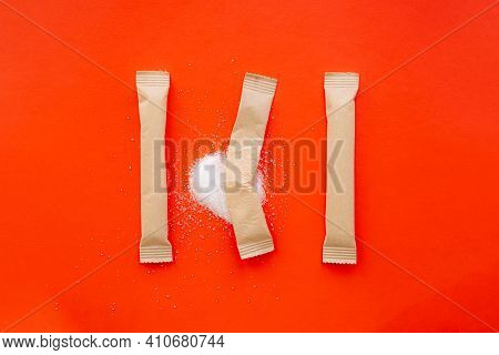 Sugar Sticks In Bright Red Backdrop, One Torn Apart With Spilled White Sugar. Sweet Consumption, Abs