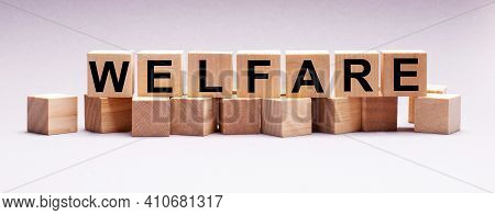 On A Light Background, Wooden Cubes With The Text Welfare