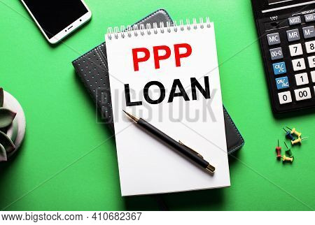 On A Green Background - A Telephone, A Calculator And A Diary With The Inscription Ppp Loan