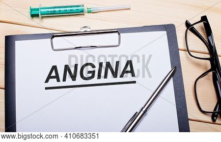 The Word Angina Is Written On A White Piece Of Paper Next To Black-rimmed Glasses, A Pen And A Syrin