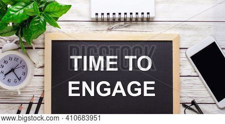 Time To Engage Written On A Black Background Near Pencils, A Smartphone, A White Notepad And A Green