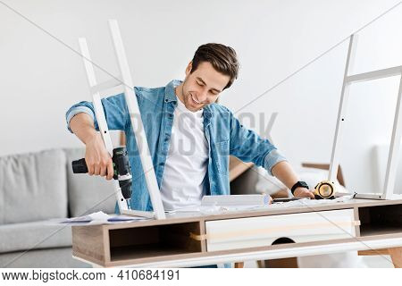 Facial Emotions Of Man With Working Tool At Home, Popular Blogger And Assembly Table. Cheerful Mille