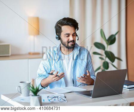 Online Tutoring. Young Arab Male Tutor In Headset Having Video Call With Students, Talking And Gestu