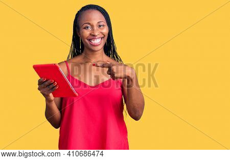 Young african american woman holding touchpad smiling happy pointing with hand and finger