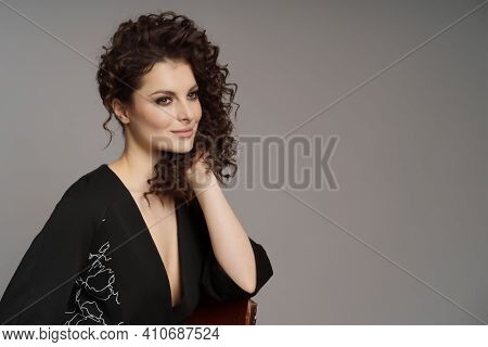 Portrait Of Cute Woman With Modern Hairdo In Stylish Clothes On Grey Background With Copy Space