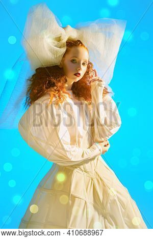 Fashion art portrait of a girl looking like a doll with lush red curly hair posing in a white haute couture dress and a huge bow. Studio portrait.