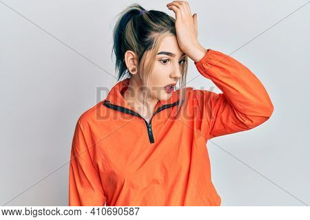 Young modern girl wearing sports sweatshirt surprised with hand on head for mistake, remember error. forgot, bad memory concept.