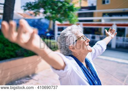 Elder senior woman with grey hair smiling happy with open arms sunbathing