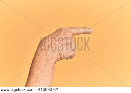 Senior caucasian hand over yellow isolated background pointing with index finger to the side, suggesting and selecting a choice