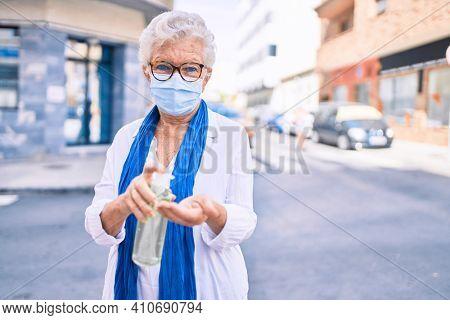 Elder senior woman with grey hair wearing coronavirus safety mask and using sanitizer gel outdoors