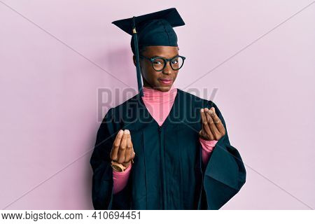 Young african american girl wearing graduation cap and ceremony robe doing money gesture with hands, asking for salary payment, millionaire business