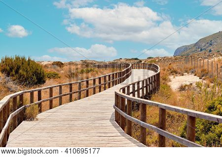 Wooden Empty Board Walk Leading Through Sand Dunes To Mediterranean Sea, Beach Of Los Arenales Del S