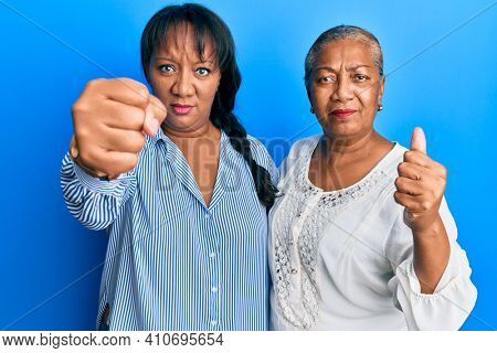 Hispanic family of mother and daughter hugging together with love annoyed and frustrated shouting with anger, yelling crazy with anger and hand raised