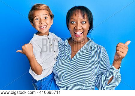 Hispanic family of mother and son hugging together with love pointing thumb up to the side smiling happy with open mouth