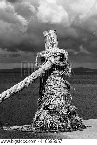 Rope On Seafront, Sea And Cloudy Sky In Sunny Summer Day. Black And White Toned Landscape. High Cont