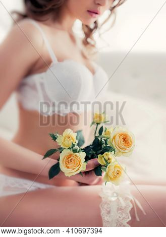 Yellow Roses And A Blurry Silhouette Of A Beautiful Sexy Bride In White Underwear And A Garter