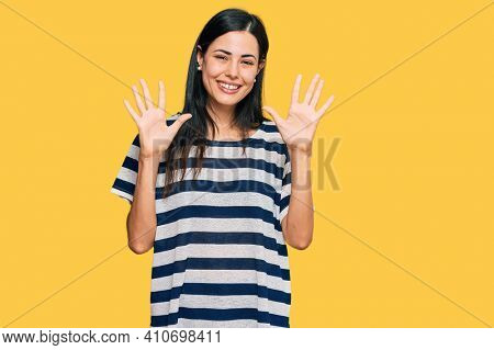 Beautiful young woman wearing casual clothes showing and pointing up with fingers number ten while smiling confident and happy.