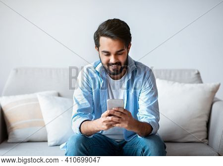 Happy Arab Man Using Smartphone At Home, Messaging With Friends While Sitting On Couch In Living Roo