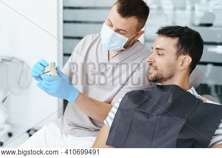 Male Dentist In Medical Mask Explaining Artificial Teeth To Smiling Patient In Clinic