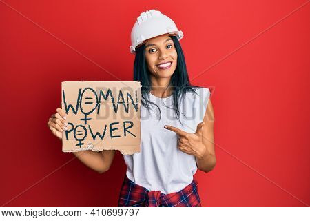 Young african american woman wearing architect hardhat holding woman power banner smiling happy pointing with hand and finger