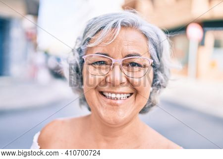 Middle age woman with grey hair smiling happy outdoors
